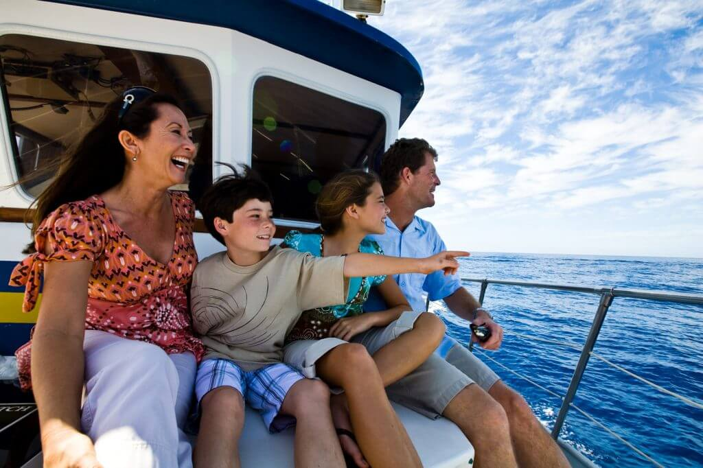 Create your ultimate Hawaii itinerary for your family. Image of a family with a boy and a girl enjoying a boat tour on Oahu.