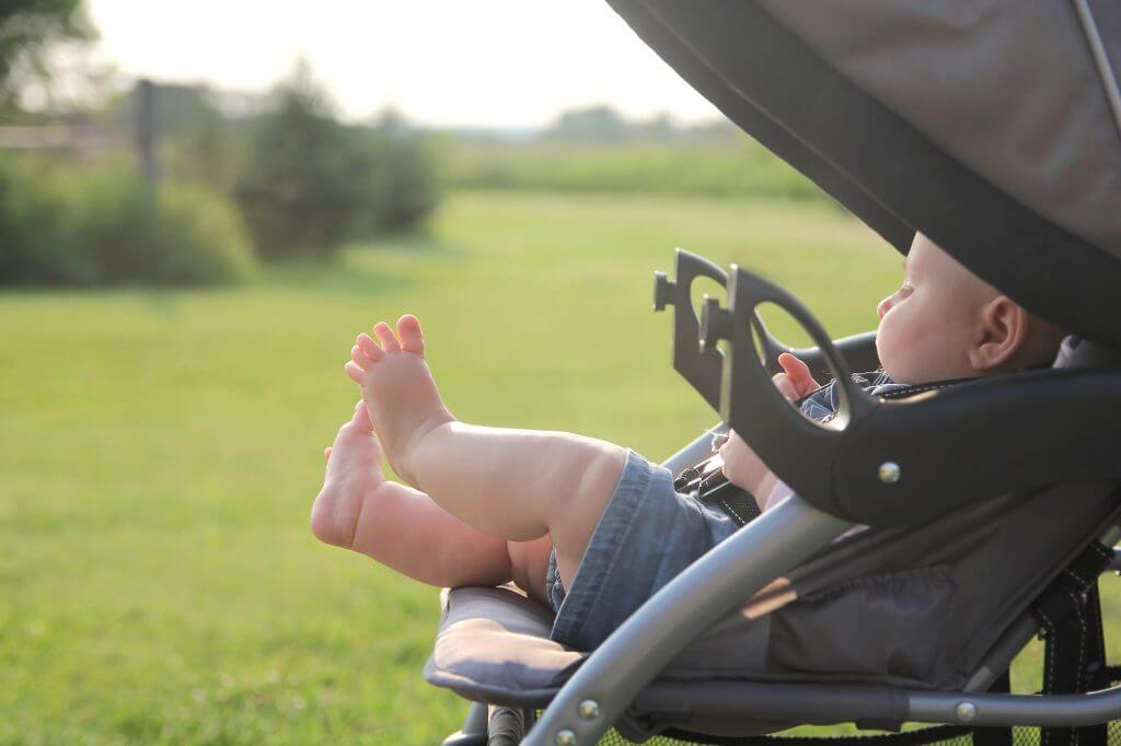 Do you need a stroller in Hawaii? Image of a baby with chunky legs in a stroller in the sunshine.