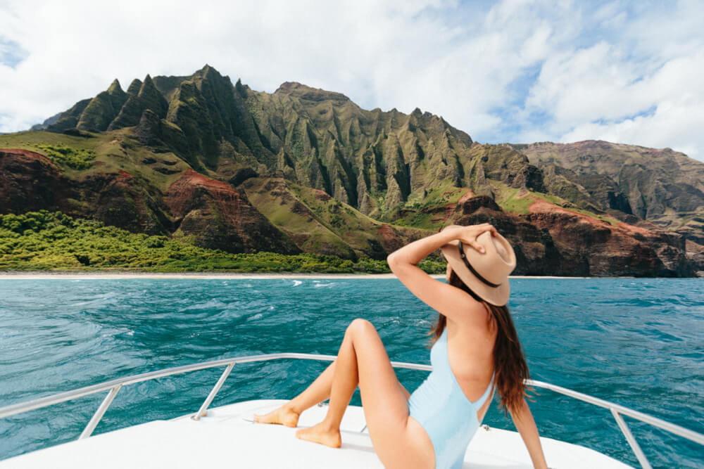 Top 15 Things to do on Your Hawaii Honeymoon featured by top Hawaii blog, Hawaii Travel with Kids: A woman sits on a boat in front of the Na Pali Coast on Kauai