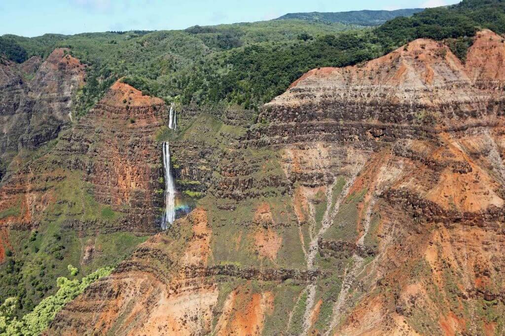 You'll definitely see Waimea Canyon on your Kauai helicopter ride. Image of a waterfall in Waimea Canyon, a top Kauai attraction.