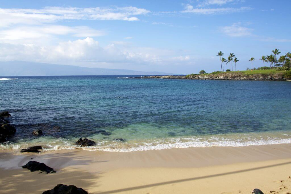 Kapalua Bay is one of the best Maui beaches for kids and is great for snorkeling. Image of a sandy beach and calm waves in Hawaii.