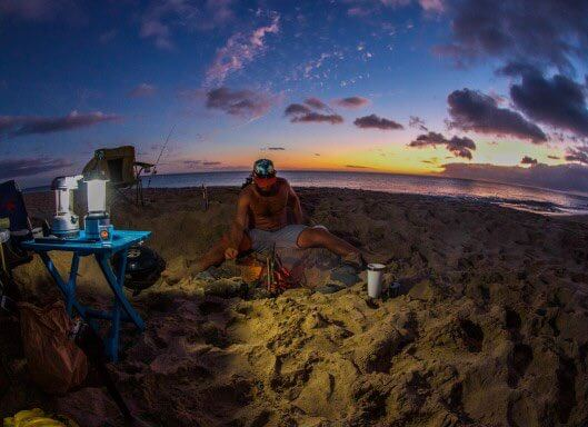 Guide to Camping in Hawaii featured by top Hawaii blog, Hawaii Travel with Kids.   You'll want to bring your own cooking equipment like this grill and cooler in the photo of a man camping in Hawaii