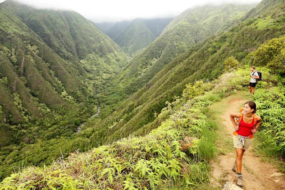 The Best Maui Hiking Trails featured by top Hawaii blog, Hawaii Travel with Kids: Hiking people on Hawaii, Waihee ridge trail, Maui, USA. Young woman and man hikers walking in beautiful lush Hawaiian forest nature landscape in mountains. Asian woman hiker in foreground.