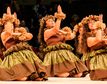 The Merrie Monarch Festival, a complete guide featured by top Hawaii blog, Hawaii Travel with Kids: Hula dancers performing a Hula Noho at the Merrie Monarch hula festival on the Big Island of Hawaii