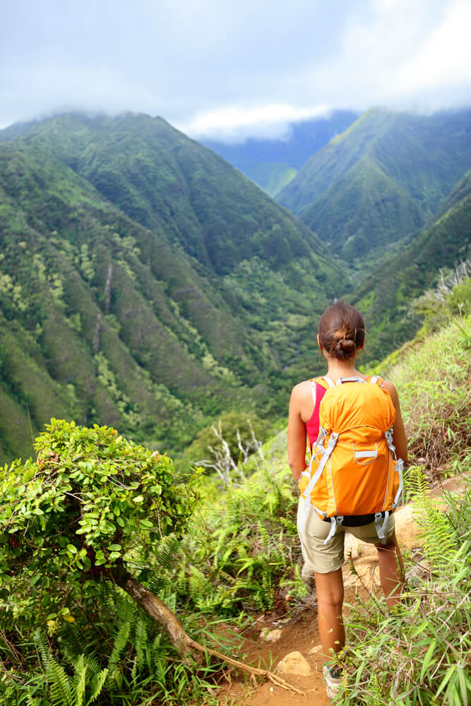 Tips for Hawaii Island Hopping featured by top Hawaii blog, Hawaii Travel with Kids: Hiking woman on Hawaii, Waihee ridge trail, Maui, USA. Young female hiker walking in beautiful lush Hawaiian forest nature landscape in mountains. Asian woman hiker wearing backpack looking at view.