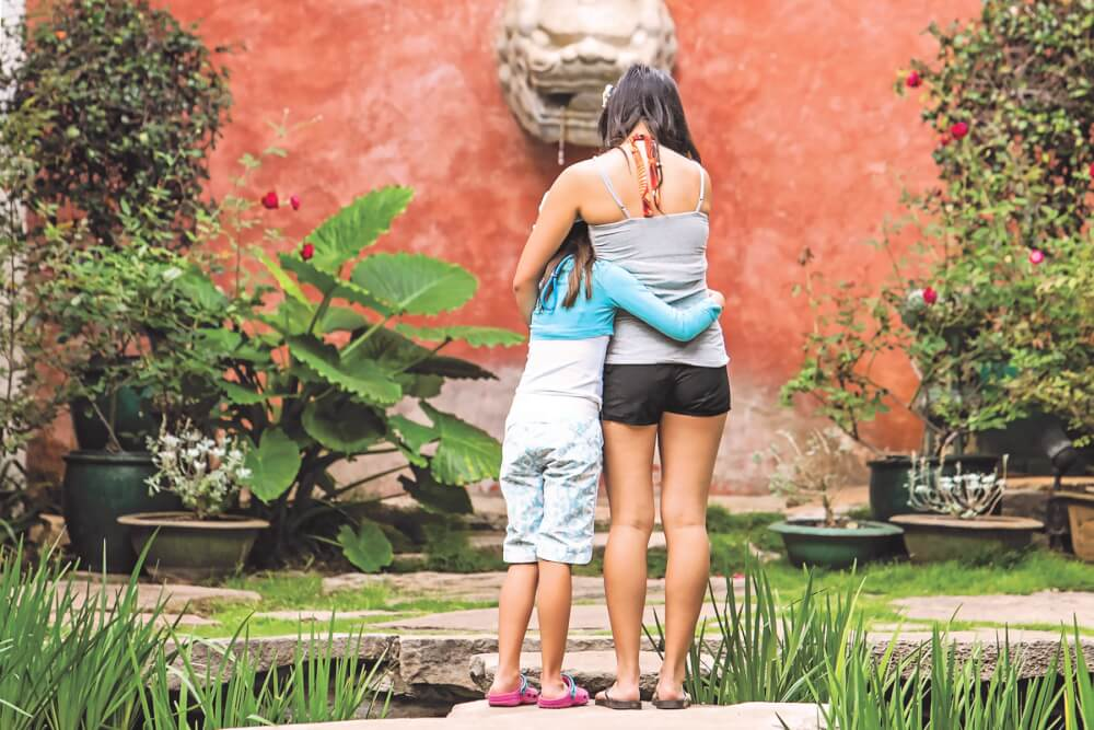 Things to Do in Hawaii with Kids: a review of Honolulu Museum of Art on Oahu featured by top Hawaii blog, Hawaii Travel with Kids: image of Girls hugging in the Asian Courtyard at the Honolulu Museum of Art on Oahu