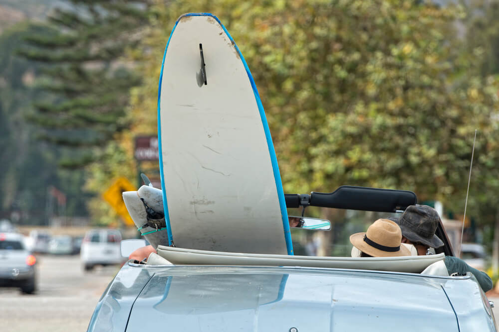 Tips for Renting a Car in Hawaii featured by top Hawaii blog, Hawaii Travel With Kids: Surf board in a convertible