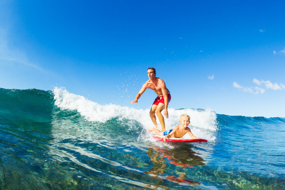 25 Amazing activities in Waikiki with kids featured by top Hawaii blog, Hawaii Travel with Kids: Father and Son Surfing Together Riding Blue Ocean Wave