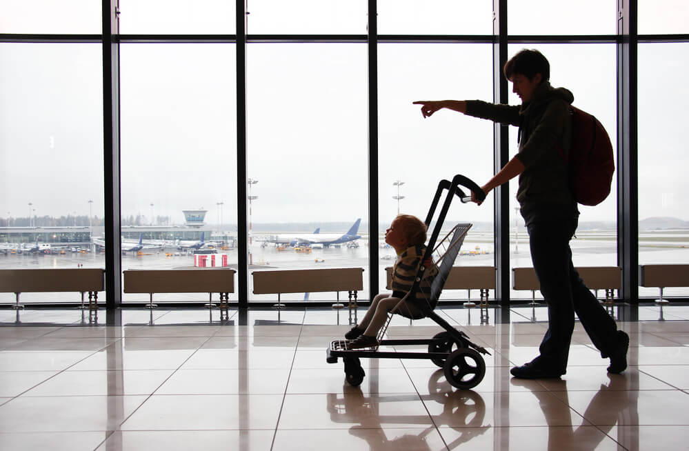 Best Travel Stroller for Hawaii featured by top Hawaii blog, Hawaii Travel with Kids: Silhouette of mother with her toddler son in stroller against the window at the airport. Mom points the direction with her finger. Family journey lifestyle.