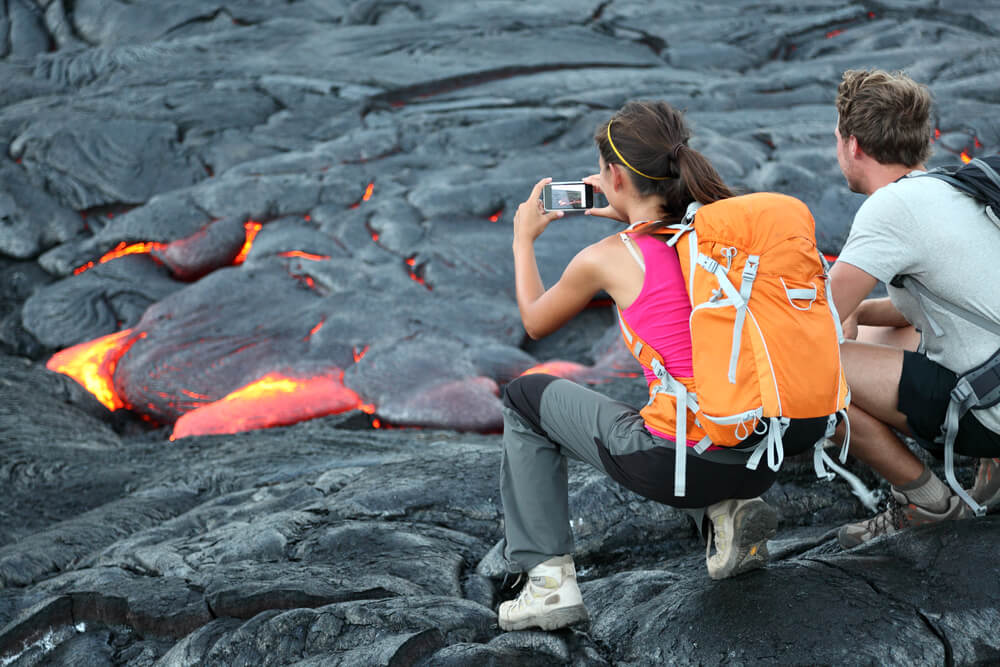 The Ultimate Guide to Hawaii Volcanoes National Park featured by top Hawaii blog, Hawaii Travel with Kids: Hawaii lava tourist. Tourists taking photo of flowing lava from Kilauea volcano around Hawaii volcanoes national park, USA.