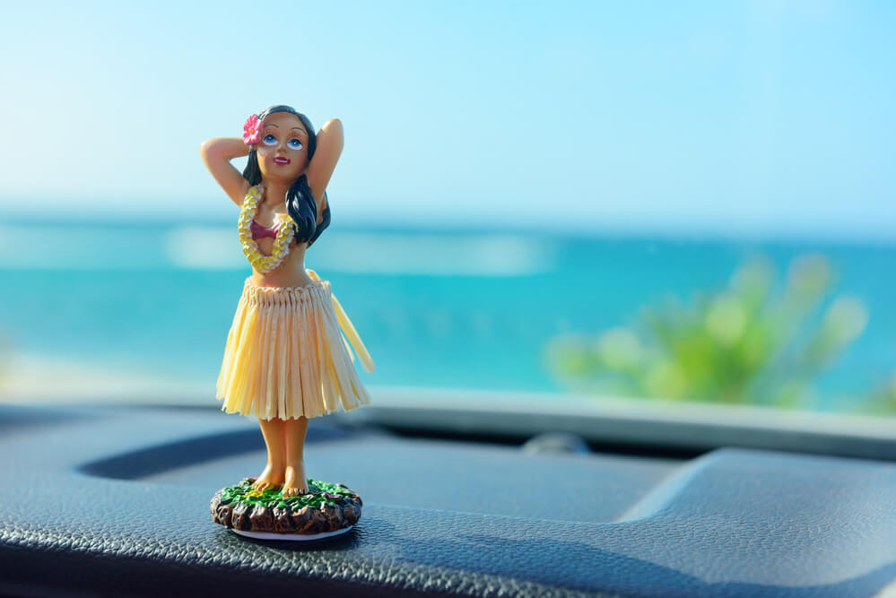 Top 13 Best Hawaiian Souvenirs to Bring Home featured by top US Hawaii blog, Hawaii Travel with Kids: Hawaii road trip - car hula dancer doll dancing on the dashboard in front of the ocean. Tourism and travel freedom concept.
