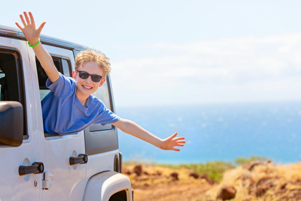 Tips for Renting a Car in Hawaii featured by top Hawaii blog, Hawaii Travel With Kids: happy positive caucasian boy in sunglasses peeking out of the car window with his hands up in the air, tropical family vacation or active road trip concept