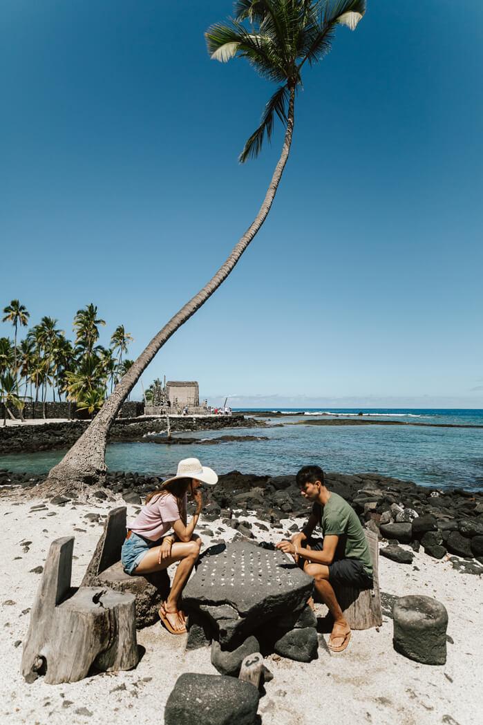 The Best Things to Do in Kona Hawaii featured by top Hawaii blog, Hawaii Travel with Kids: Visitors play konane, a checkers-like game, at Puuhonua o Honaunau