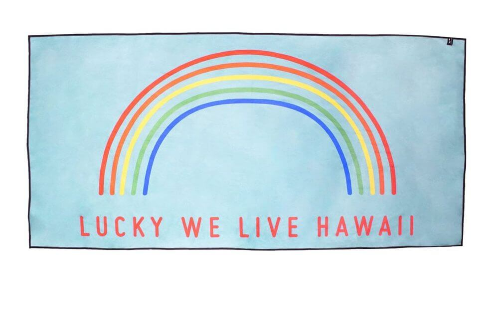"Top 15 Best Kauai Souvenirs featured by top Hawaii blog, Hawaii Travel with Kids: Travel towel with a rainbow that says ""Lucky We Live Hawaii."""