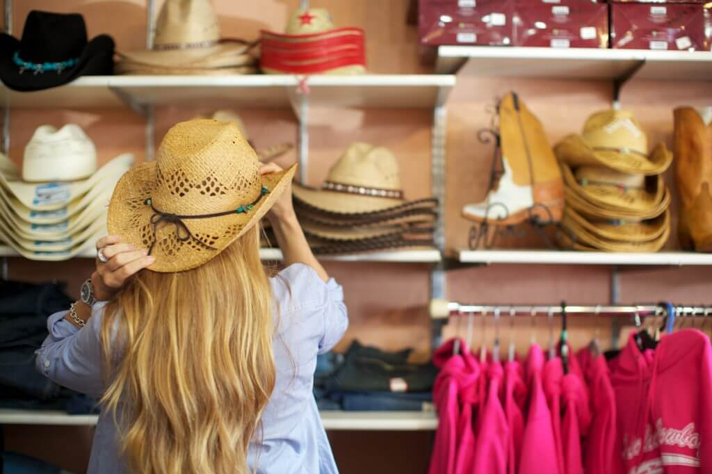 Woman trying on hats while shopping in Makawao, Maui
