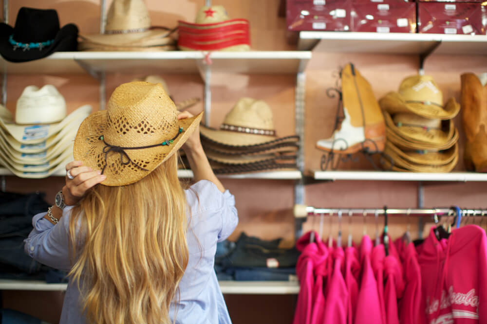 The Ultimate Guide to Shopping on Maui featured by top Hawaii blog, Hawaii Travel with Kids: Woman trying on hats while shopping in Makawao, Maui