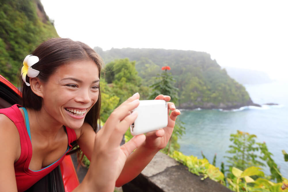 Tips for Renting a Car in Hawaii featured by top Hawaii blog, Hawaii Travel With Kids: Tourist on Hawaii taking photo with camera phone during car road trip on the famous Road to Hana
