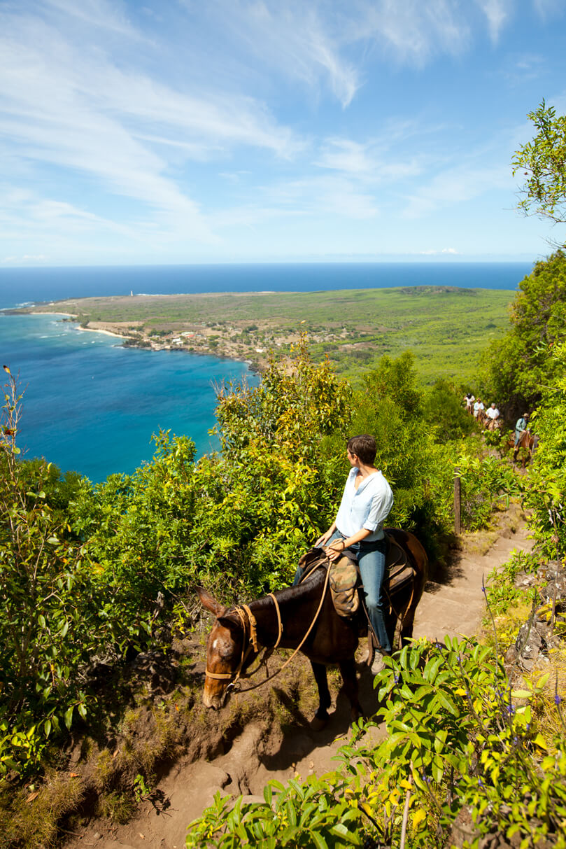 17 Historical Places in Hawaii to Visit with Kids featured by top Hawaii blog, Hawaii Travel with Kids: View of Kalaupapa as mules ride up in Molokai