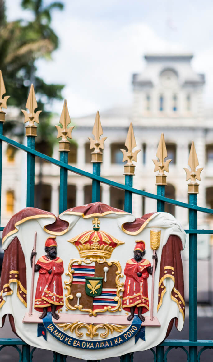 17 Historical Places in Hawaii to Visit with Kids featured by top Hawaii blog, Hawaii Travel with Kids: Royal Seal on a gate to Iolani Palace on Oahu