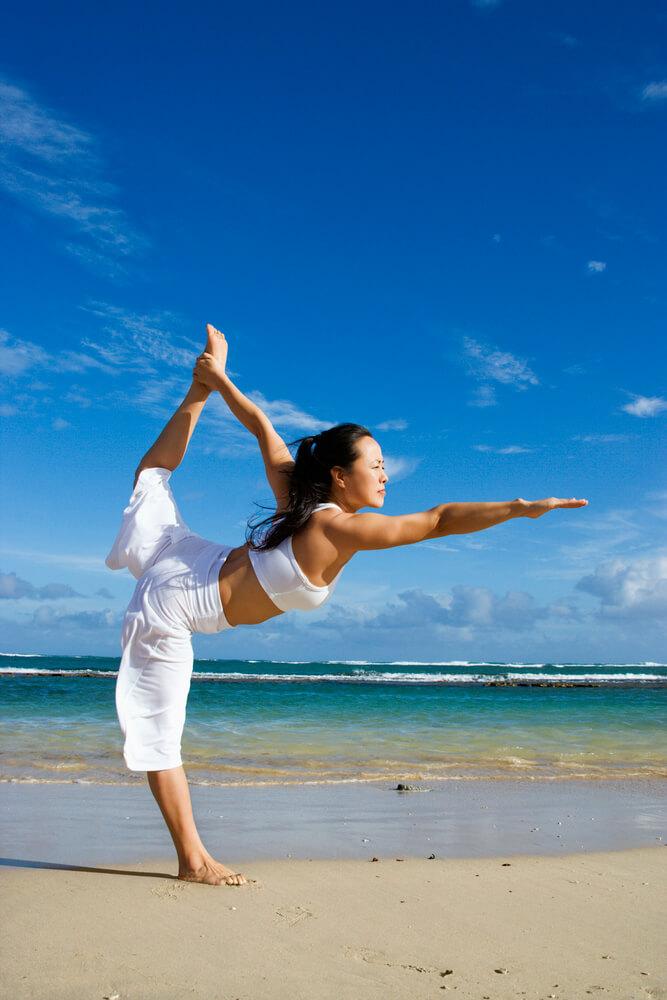 Image of a woman doing yoga on the beach maui