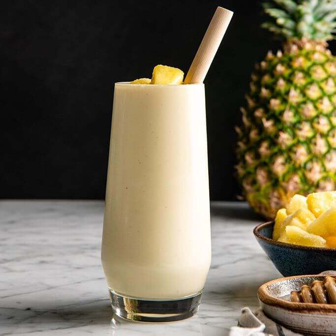 Hawaiian Tropical Smoothie Recipes to Make at Home featured by top Hawaii blog, Hawaii Travel with Kids: front view of a pineapple smoothie in a glass