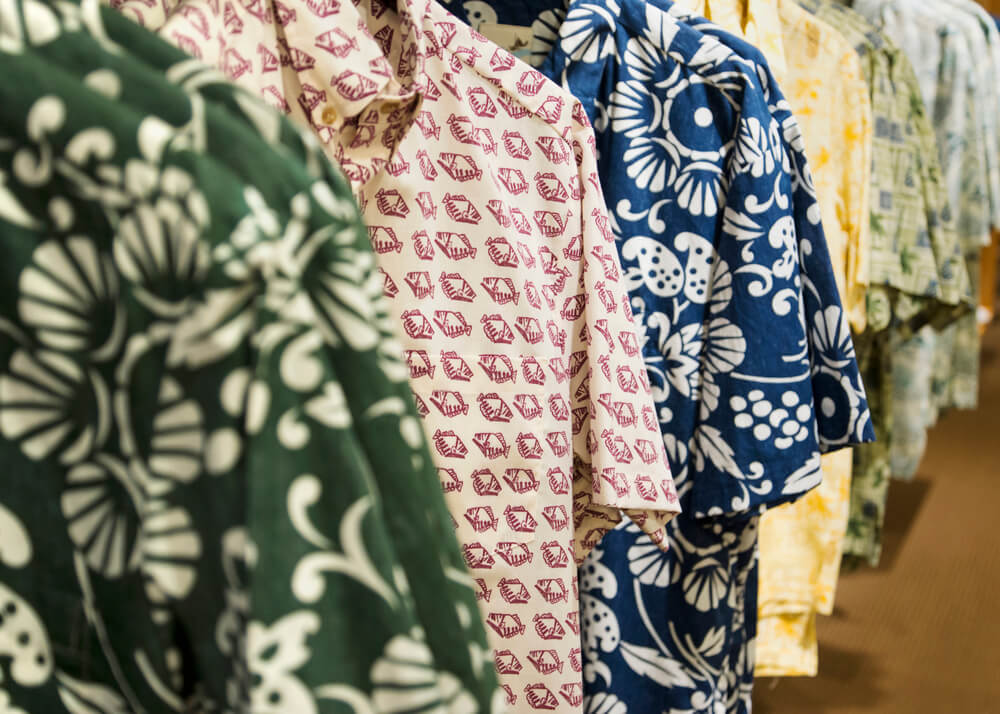 Hawaii Lei Day Celebrations + Activities for Kids featured by top Hawaii blog, Hawaii Travel with Kids: short sleeve Aloha shirts for sale in a department store