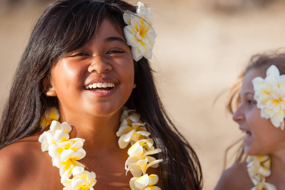 Hawaii Lei Day Celebrations + Activities for Kids featured by top Hawaii blog, Hawaii Travel with Kids: Pretty Hula Girl at the beach wearing a handmade flower lei