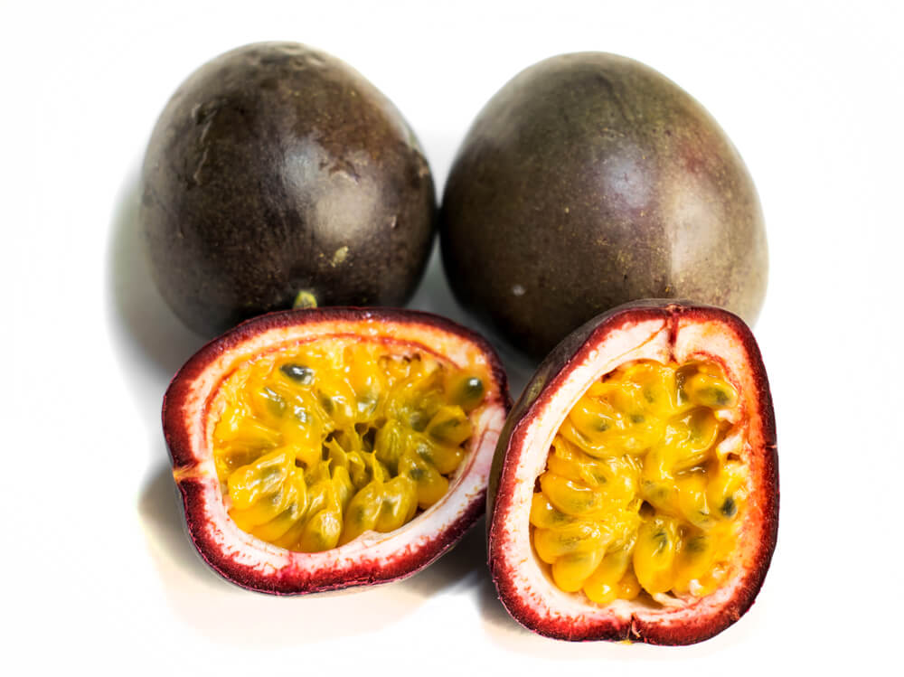 15 Hawaiian Fruits to Try featured by top Hawaii blog, Hawaii Travel with Kids: Passion fruit ( Passiflora edulis).3 fruits. The fruit is cut in two halves. Isolated on a white background