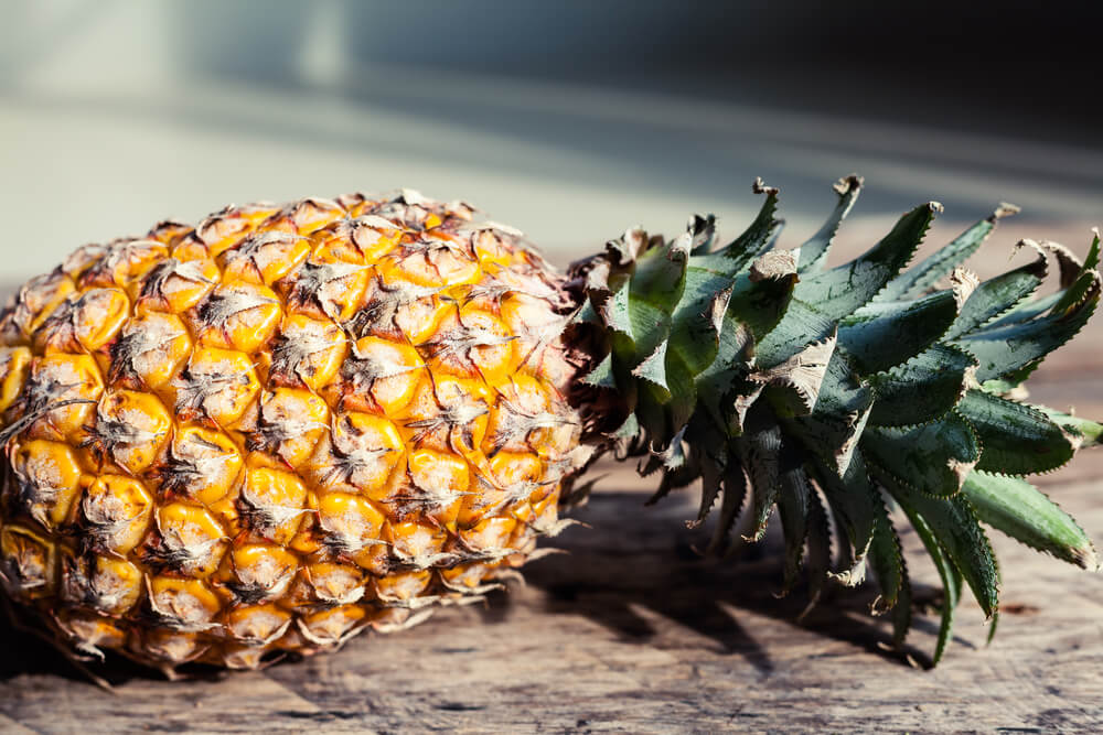 15 Hawaiian Fruits to Try featured by top Hawaii blog, Hawaii Travel with Kids: Fresh pineapple on a table