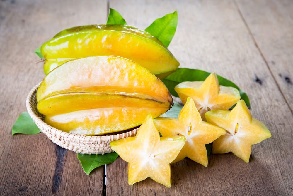15 Hawaiian Fruits to Try featured by top Hawaii blog, Hawaii Travel with Kids: Star fruit on wood background .