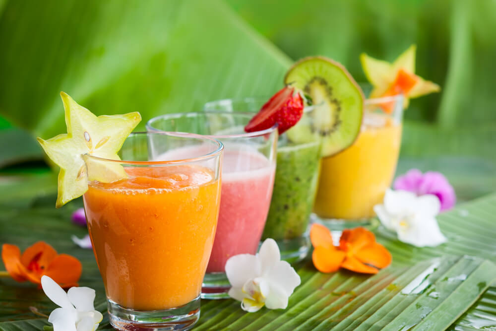 Hawaiian Tropical Smoothie Recipes to Make at Home featured by top Hawaii blog, Hawaii Travel with Kids: Assortment of fresh tropical fruits smoothies on the green banana leaves