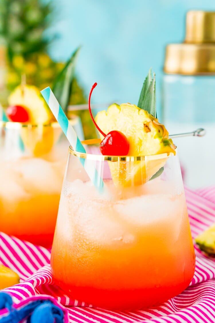 40 Hawaiian Cocktails To Try At Home featured by top Hawaii blog, Hawaii Travel with Kids: A Mai Tai is a boozy blend of coconut and spiced rum, triple sec, orange and pineapple juices, and a splash of grenadine. Mix up a batch for a taste of the tropics to enjoy with friends and family this summer.