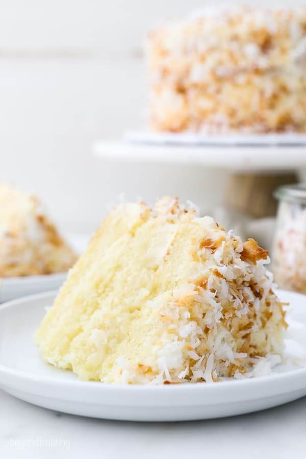 61 Delicious Coconut Dessert Recipes Perfect for Summer featured by top Hawaii blog, Hawaii Travel with Kids: A closeup of a layered coconut cake on a white rimmed plate, the cake stand is blurred out in the background