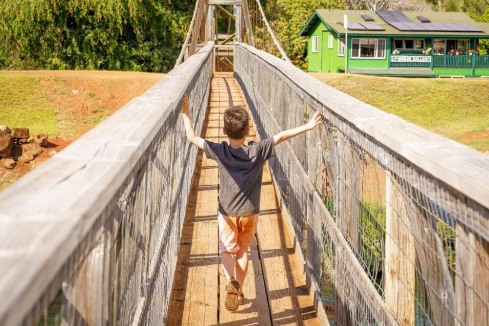 Top 12 Best Photo Opportunities on Kauai featured by top Hawaii travel blog, Hawaii Travel with Kids: The Hanapepe Swinging Bridge is a top photo spot on Kauai.