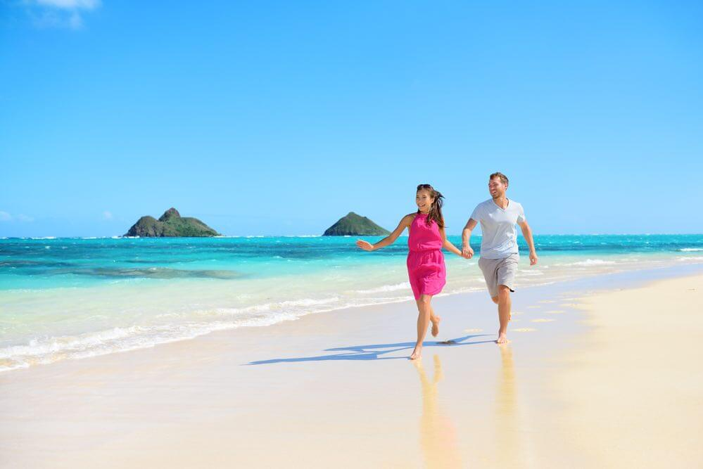 Top 15 Things to do on Your Hawaii Honeymoon featured by top Hawaii blog, Hawaii Travel with Kids: Beach happy couple on running having fun on Hawaii. Romantic couple joyful and full of happiness on travel vacation on Lanikai beach, Oahu, Hawaii, USA with Mokulua Islands. Asian woman, Caucasian man