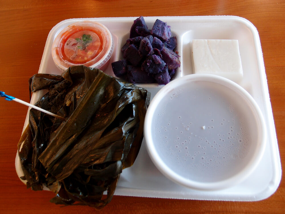 Hawaiian Lau Lau plate Served with Fresh/Day Old Poi in bowl, 'Uala (sweet Potato), Haupia with Lomi Salmon in a plastic container on a Styrofoam plate on a table.