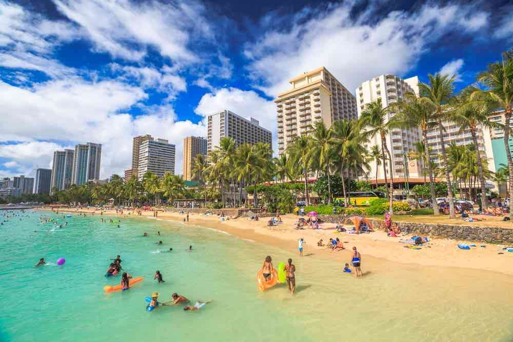25 Amazing activities in Waikiki with kids featured by top Hawaii blog, Hawaii Travel with Kids: Waikiki, Oahu, HI - August 27, 2016: summertime in crowded Prince Kuhio Beach also called The Ponds because a concrete wall makes the water calm. Kuhio Beach is a section of Waikiki Beach.