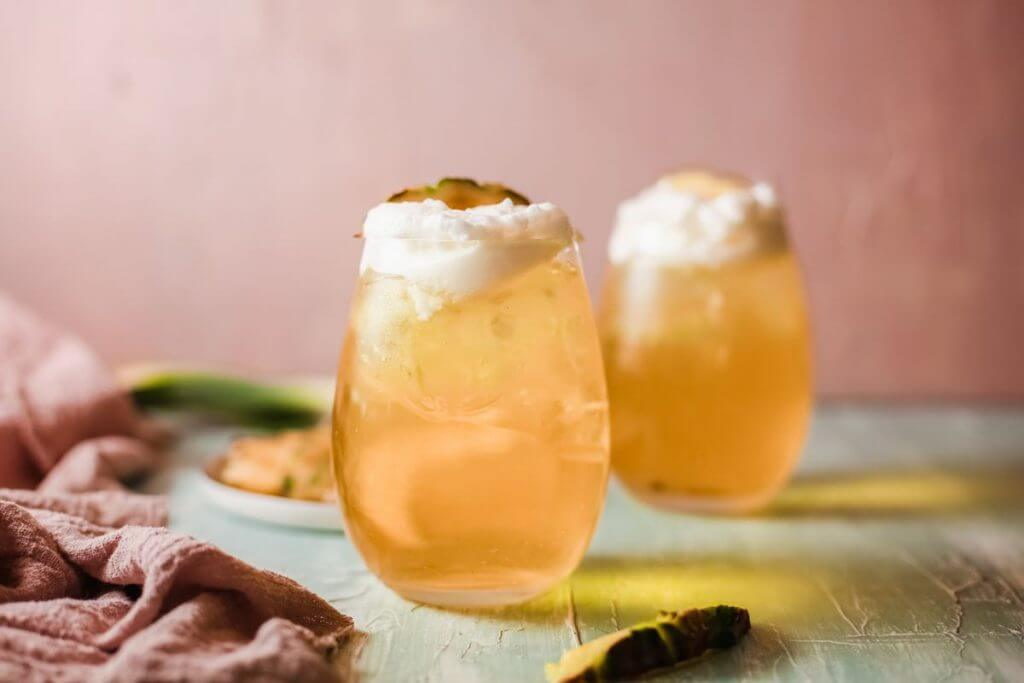 The best Hawaiian Mai Tai cocktail recipe from Hawaii blog Hawaii Travel with Kids. Image of two glasses filled with Mai Tai cocktails.