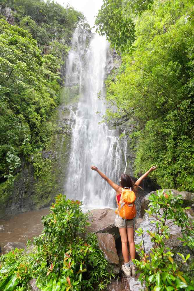 Road to Hana Guide: 15 Things to Know Before You Drive the Road to Hana featured by top Hawaii blog, Hawaii Travel with Kids: Happy hiker - Hawaii tourists hiking by waterfall. Woman cheering during travel on the road to Hana on Maui, Hawaii. Ecotourism concept image with happy female hiker.