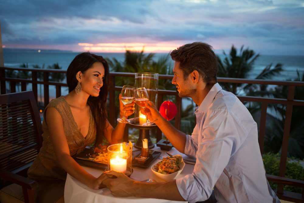 The Ultimate Hawaii Honeymoon Packing List featured by top Hawaii blog, Hawaii Travel with Kids: young couple enjoying a romantic dinner by candlelight, outdoor on Hawaii honeymoon