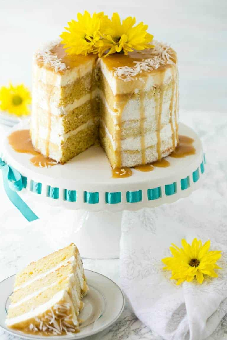 61 Delicious Coconut Dessert Recipes Perfect for Summer featured by top Hawaii blog, Hawaii Travel with Kids: mango cake on a cake stand with slice removed