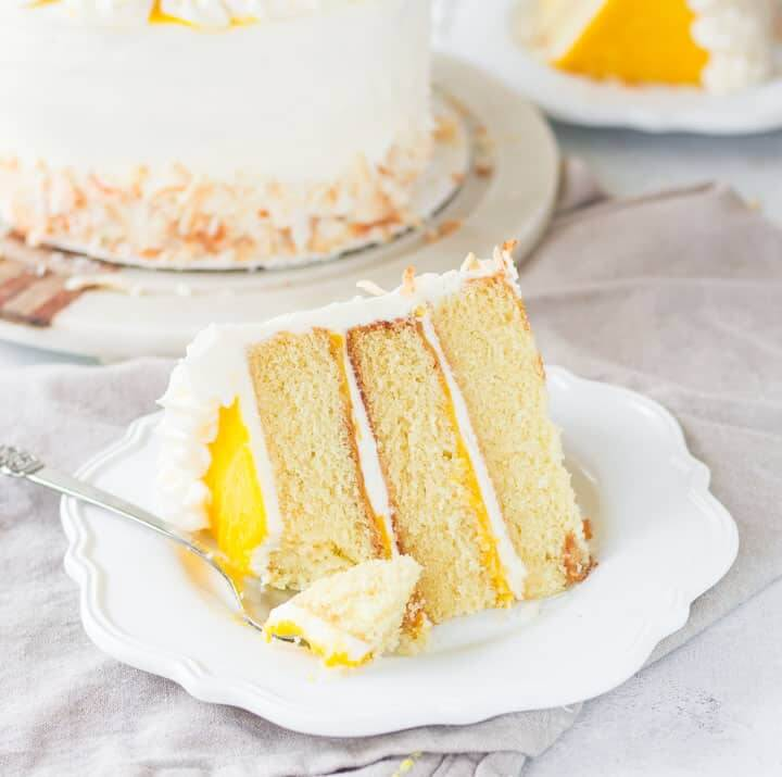 61 Delicious Coconut Dessert Recipes Perfect for Summer featured by top Hawaii blog, Hawaii Travel with Kids: slice of mango coconut cake sitting on a plate with a fork taking a bite out of it