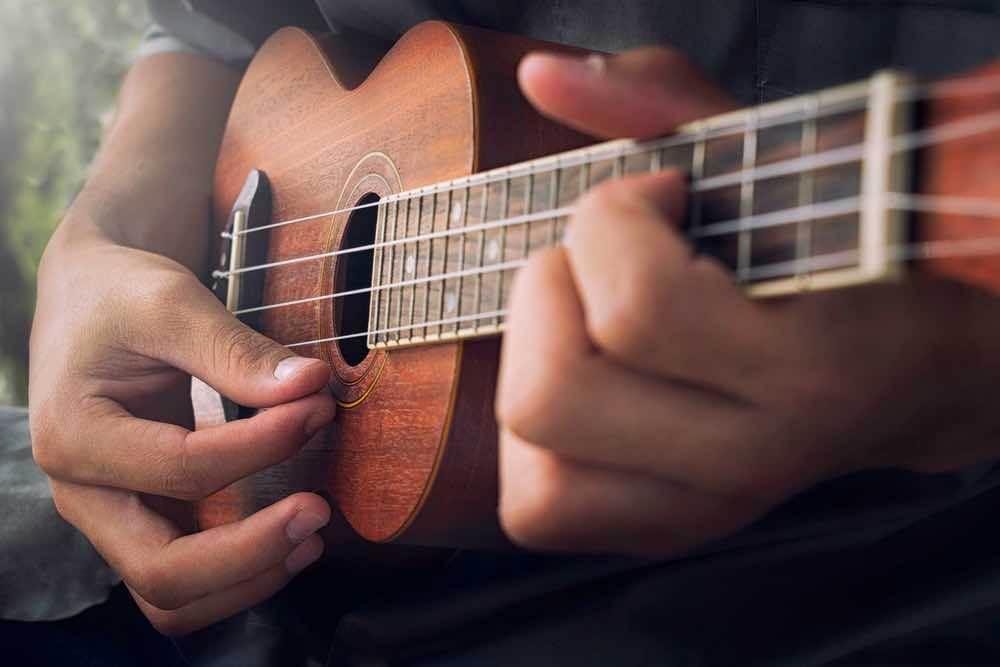 Top 10 Romantic Hawaii Beach Proposal Ideas + Locations featured by top Hawaii blog, Hawaii Travel with Kids: Man playing ukulele in Hawaii