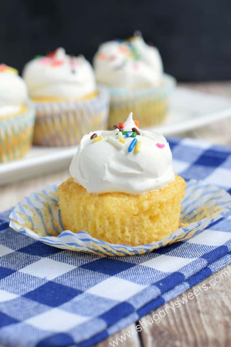Pineapple Dessert Recipe Roundup by top Hawaii blog Hawaii Travel with Kids: Pineapple cupcake topped with whipped cream and sprinkles unwrapped on a blue checkered napkin.