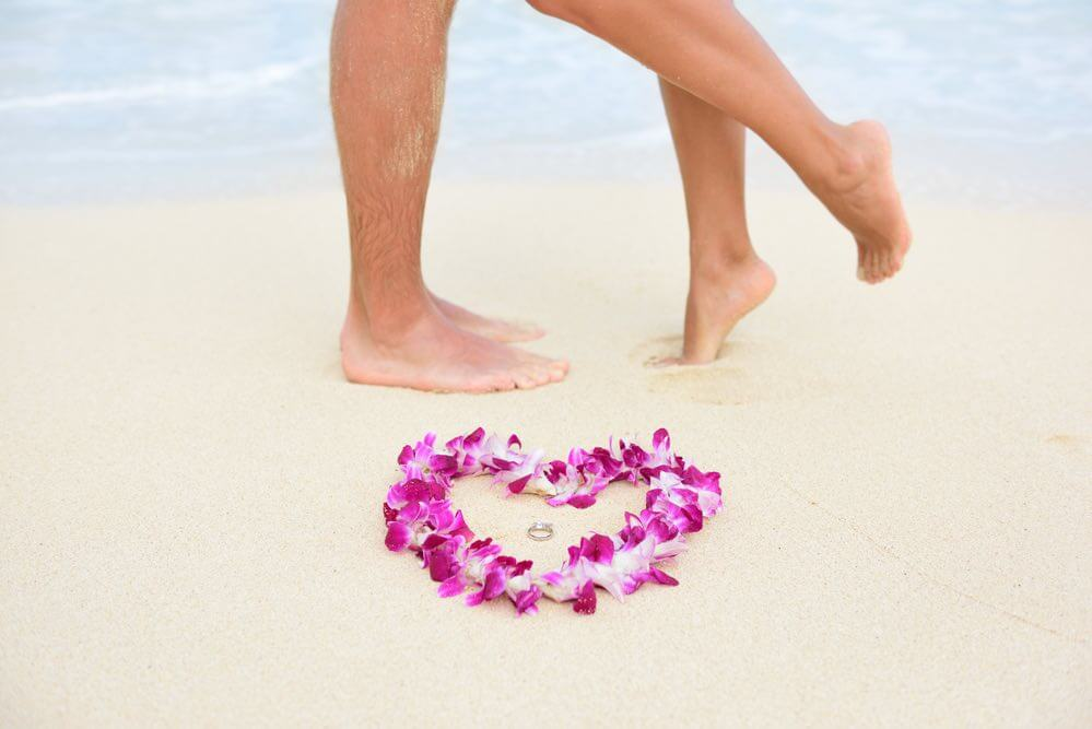 Top 10 Romantic Hawaii Beach Proposal Ideas + Locations featured by top Hawaii blog, Hawaii Travel with Kids: Beach wedding just married couple kissing with feet in background and rings in focus in heart shape lei flower necklace. Hawaiian marriage love concept.