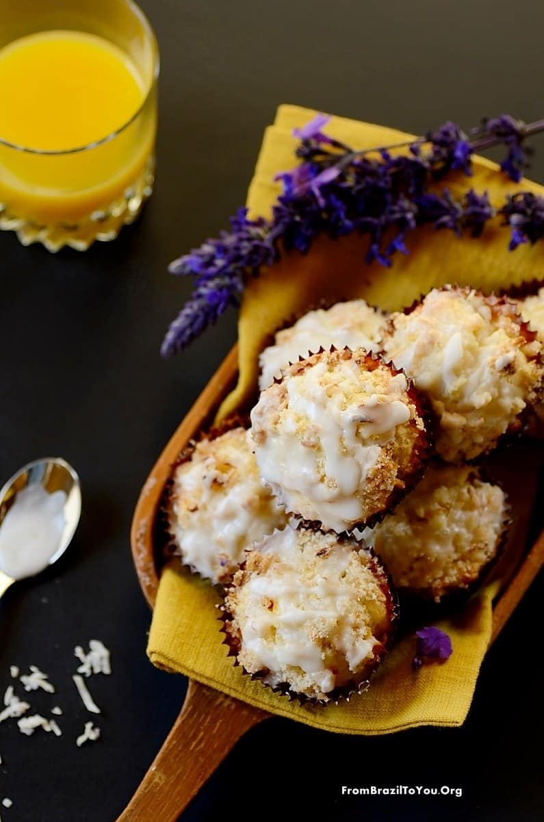 Best Mango dessert recipes by top Hawaii blog Hawaii Travel with Kids: Serving Mango Coconut Streusel Muffins in a platter with flowers on the side and a glass of juice