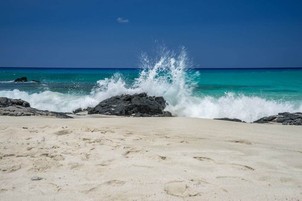 Top 10 Romantic Hawaii Beach Proposal Ideas + Locations featured by top Hawaii blog, Hawaii Travel with Kids: Manini'owali Beach also known as Kua Bay is known for it's white sand beach and crystal clear water