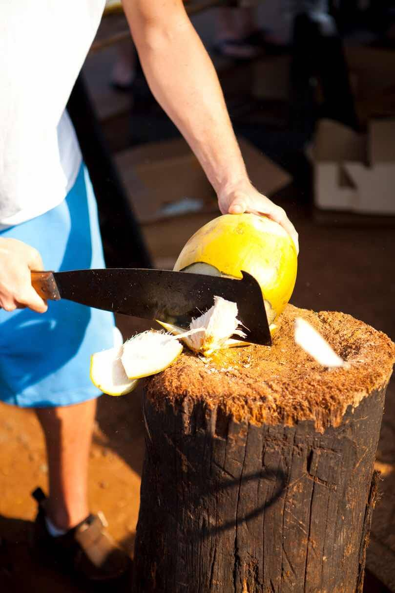 7 Best Maui Farmers Markets Worth Checking Out featured by top Hawaii travel blog, Hawaii Travel with Kids: Image of a man chopping a coconut with a machete.