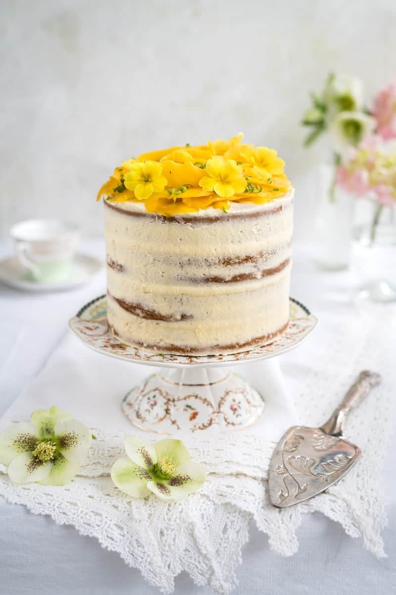 Best Mango dessert recipes by top Hawaii blog Hawaii Travel with Kids: Tall vegan layer cake topped with a mango rose and edible flowers