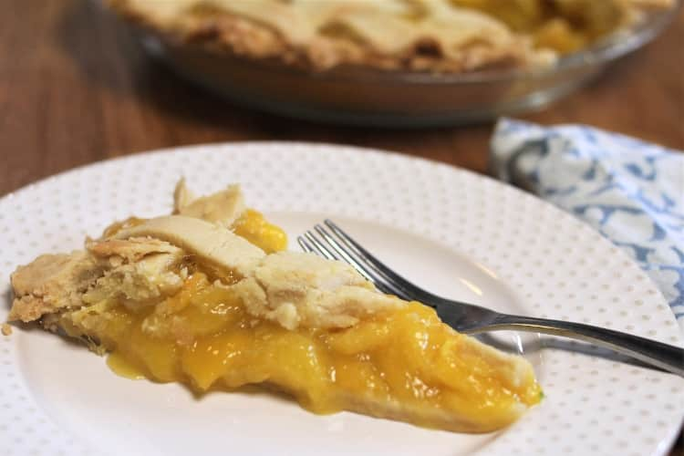 Best Mango dessert recipes by top Hawaii blog Hawaii Travel with Kids: image of a slice of mango lime pie and a fork on white plate with gold dots, with a pie in a pie pan in the background, and blue and white napkin beside the plate